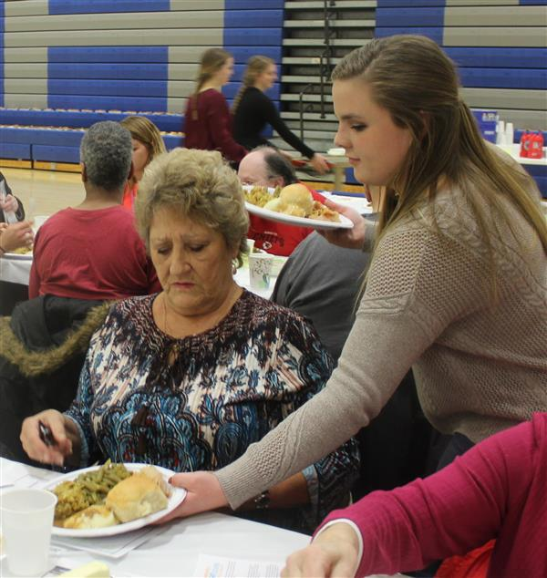 HHS student Kelsey Campbell serves a dinner to a banquet attendee