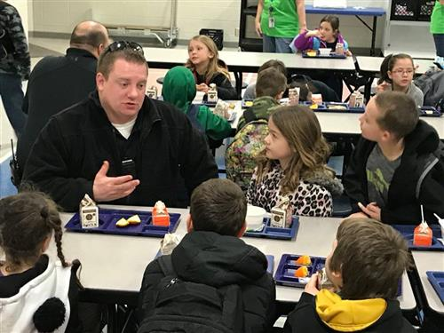 Officer Mikelson talks with students at HES during breakfast