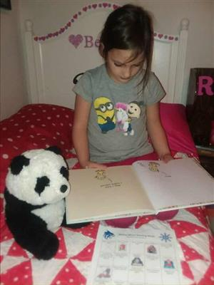 a student reads to her stuffed animal in bed