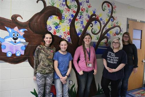 HHS artists pose in front of the reading tree mural