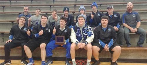 wrestling team poses with first place plaque