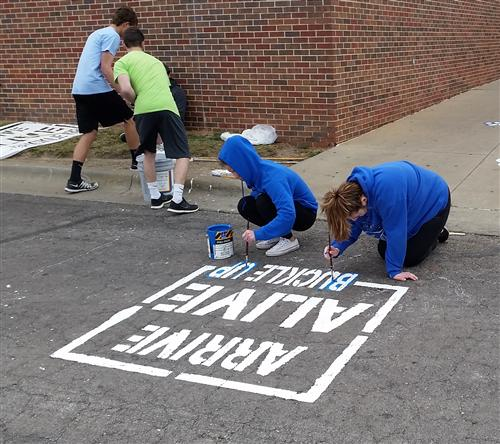 SADD members paint buckle up messages in parking lots